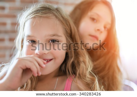 Beautiful little sisters smiling on the background of a brick wall. - stock photo