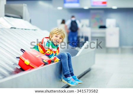 Beautiful little tired kid boy at the airport, traveling. Happy child waiting with kids suitcase on baggage carousel. Canceled flight due to pilot strike.