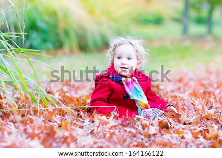 Beautiful little toddler girl in a red coat playing with colorful leaves in an autumn park