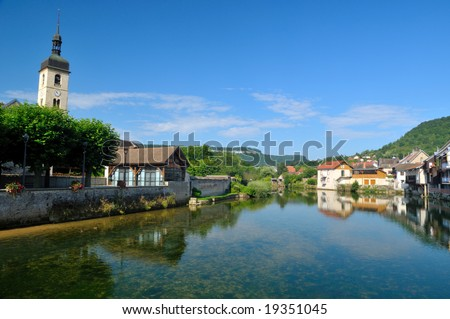 Beautiful little town at the Loue river in France - stock photo