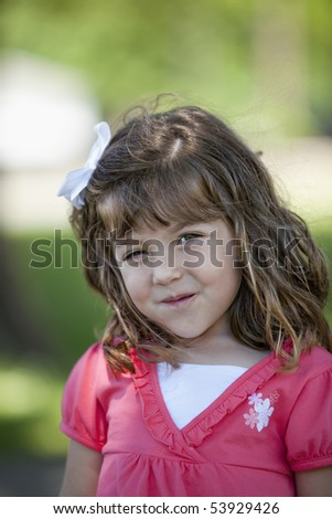 Beautiful little 3 year old girl brunette with white bow in her hair and pink and white shirt standing outdoors in wooded area