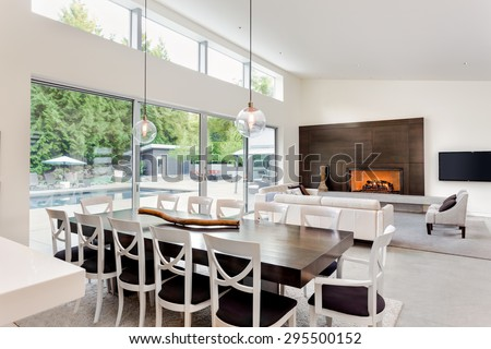 Beautiful living room/great room/family room with fireplace and dining room and vaulted ceilings in new luxury home. Includes sliding glass doors with view of backyard patio and pool - stock photo