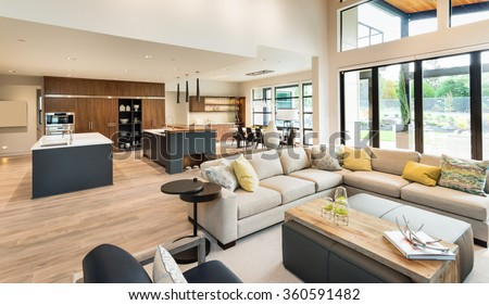 Beautiful living room interior in new luxury home with view of kitchen. Home interior with hardwood floors and open floor plan showing dining room, kitchen, and living room. Has high vaulted ceilings. - stock photo