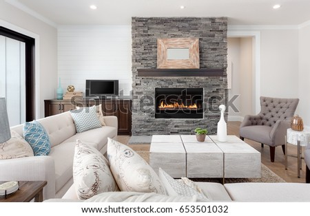 Beautiful living room interior with hardwood floors and fireplace in new luxury home. Couches at right angles face armchairs and fireplace surround stretches to ceiling and is bordered by credenza.