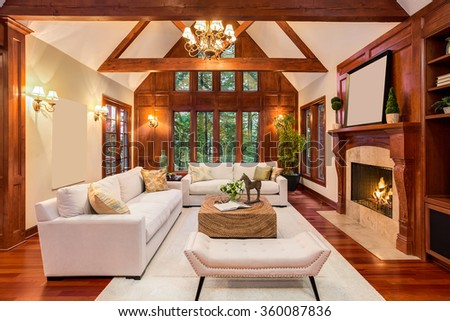 Beautiful living room interior with hardwood floors and fireplace in new luxury home. Includes chandelier, vaulted ceilings, and view of trees through windows. - stock photo