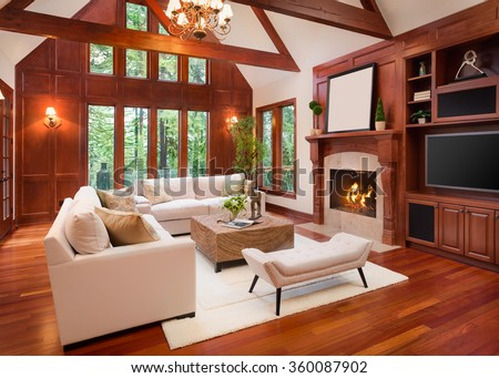 Beautiful living room interior with hardwood floors and fireplace in new luxury home. Includes vaulted ceilings. Lush green trees fill the exterior view. - stock photo