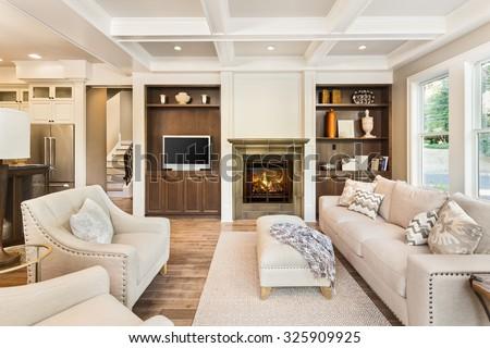 hardwood living room. Beautiful living room interior with hardwood floors  coffered ceiling and roaring fire in fireplace Living Room Interior Hardwood Floors Stock Photo