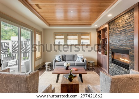 Beautiful living room with hardwood floors, ceiling, and fireplace in new luxury home - stock photo