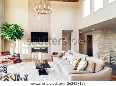 Beautiful living room with hardwood floors, tv, chandelier, and fireplace - stock photo