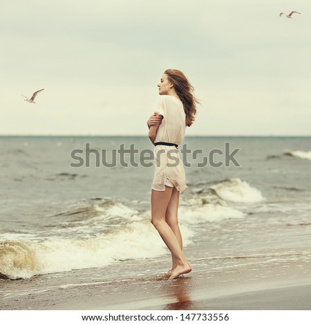 Beautiful lonely girl on the beach hugging herself - stock photo