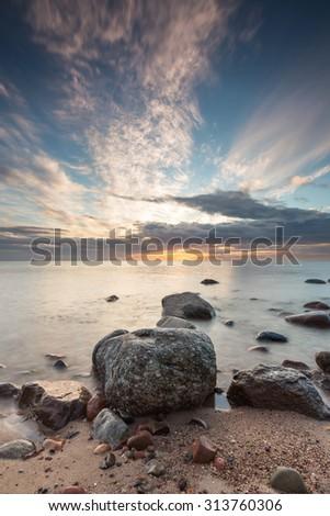 Beautiful long exposure landscape of rocky sea shore. Tranquil scene of Baltic sea. - stock photo