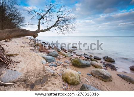 Beautiful long exposure landscape of rocky sea shore. Tranquil scene of Baltic sea near Gdynia in Poland. - stock photo