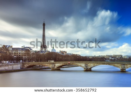 Beautiful long exposure view of the river Seine in Paris, with the Eiffel tower in the background, on a cloudy winter day  - stock photo