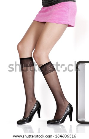 Beautiful long female legs wearing black stockings and heels  - stock photo