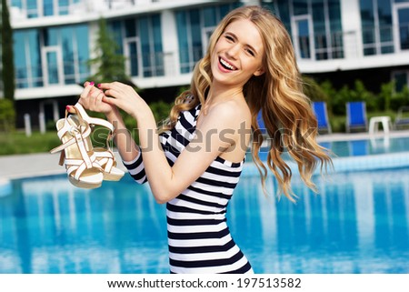 Beautiful long hair blonde female model in stripped dress posing by the pool - stock photo
