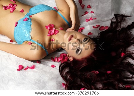 Beautiful long hair woman lying in the bed of roses. - stock photo