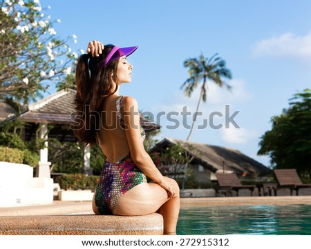beautiful long hair young woman in bikini posing by the pool. Outdoors lifestyle portrait - stock photo