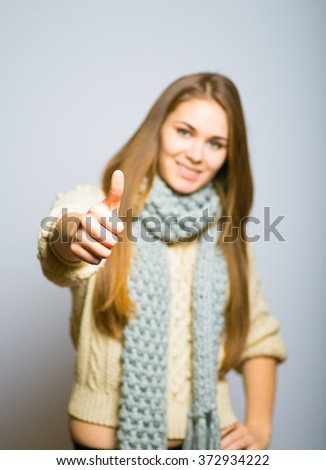 beautiful long-haired blond girl showing thumbs up, everything is OK, the concept of winter, photo studio, portrait of a woman isolated on gray background - stock photo