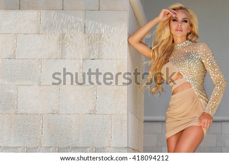 Beautiful long-haired blond woman in a short dress crystal flesh-colored against a brick wall in gold high heels