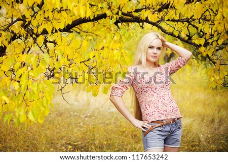 beautiful long-haired blonde girl in the autumn park. outdoor shot - stock photo