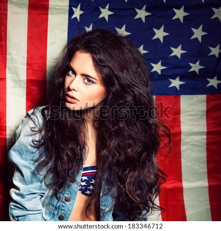 beautiful long haired posh girl  against usa flag poses for the camera - stock photo