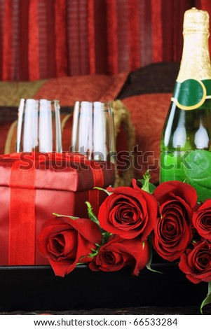 Beautiful long stem red roses with gift, wine and glasses in a breakfast tray on a bed.