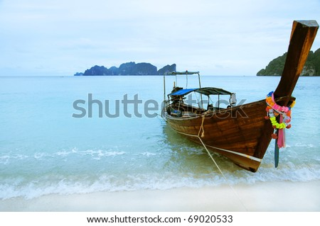 beautiful long tail boat on the sand seashore