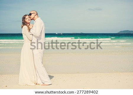 Beautiful love couple in white dress on luxury beach with white sand near blue sea - stock photo