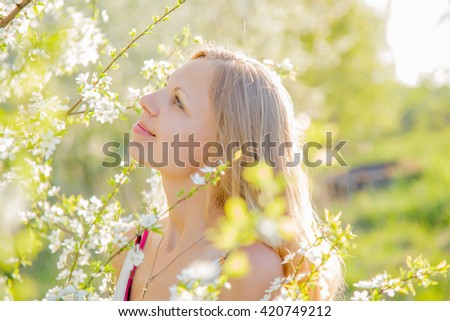 Beautiful, lovely and young woman at the tree flowers in spring sunlight.