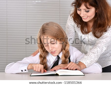 beautiful lovely girl with her mother learns the table on a light background with a book