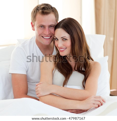 Beautiful lovers embracing lying in bed at home - stock photo