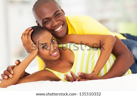 beautiful loving african american couple lying in bed - stock photo