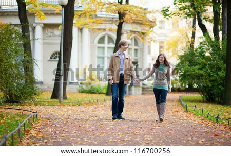 Beautiful loving couple enjoying a fall day in park - stock photo