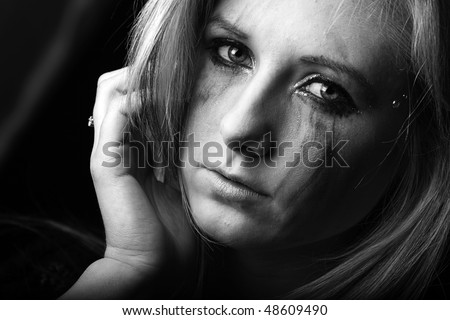 beautiful low key dramatic image of a pensive and crying young woman