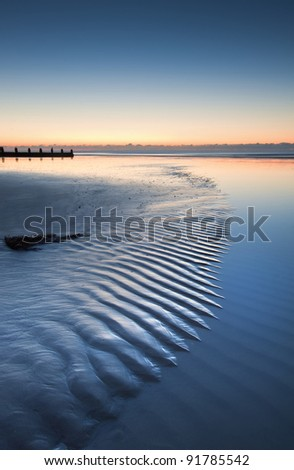 Beautiful low point of view along beach at low tide out to sea with vibrant sunrise sky - stock photo