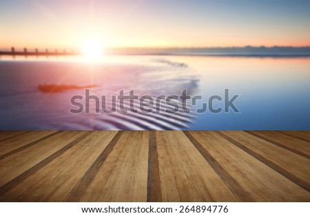 Beautiful low point of view along beach at low tide out to sea with vibrant sunrise sky with wooden planks floor - stock photo