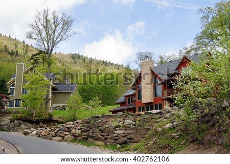 Beautiful luxurious houses or cottages in the hills spring time - stock photo