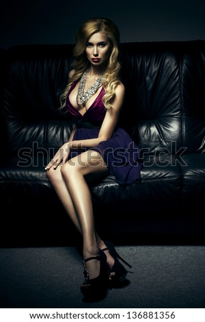 Beautiful luxurious woman sitting on a  couch - stock photo