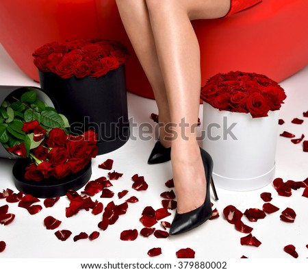 Beautiful luxury fashionable woman legs in high hills  with roses bouquet and petals - stock photo