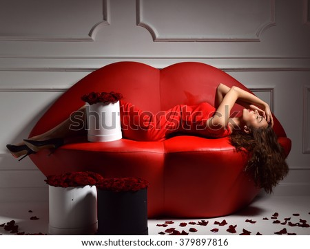 Beautiful luxury fashionable woman lying on red lips sofa couch and red dress smiling lughing with roses bouquet, petals  - stock photo