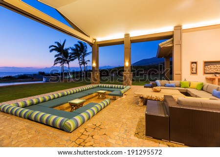 Beautiful Luxury Home, Exterior Patio Lounge at Sunset - stock photo