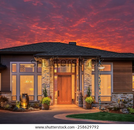 Beautiful Luxury Home Exterior with Colorful, Fiery Sunset Backdrop - stock photo