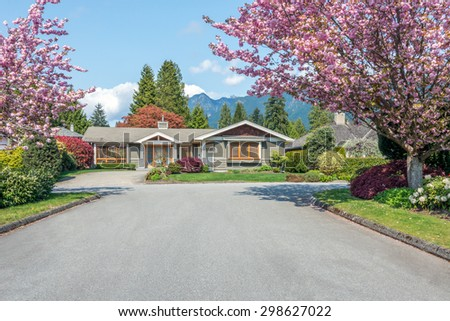 Beautiful luxury house with cherry blossom and mountains in the background. Home exterior. - stock photo