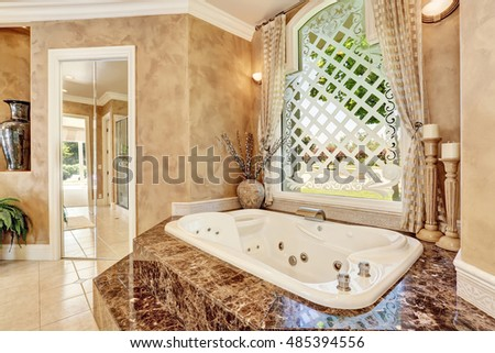 Beautiful luxury marble bathroom interior in beige color. Great bathtub with steps and large window with nice decor. Northwest, USA