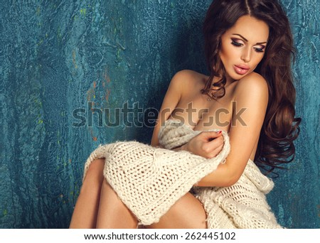 Beautiful luxury sexy brunette woman relax sitting naked in warm wool knit plaid on blue background with copy space. Spa beauty and healthy life concept - stock photo