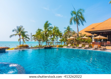 Beautiful luxury Swimming pool with palm tree and sea background in hotel pool resort - Boost up color Processing - stock photo