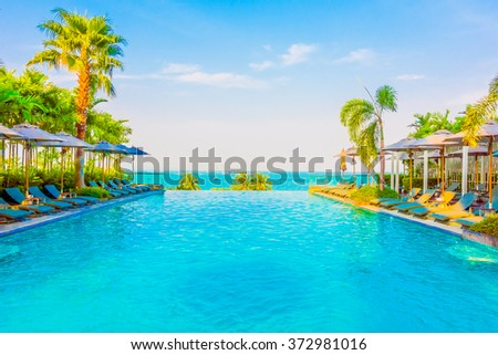 Beautiful luxury swimming pool with umbrella and chair in luxury hotel resort - Boost up color Processing style - stock photo