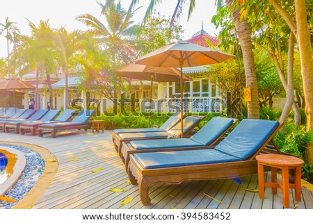 Beautiful luxury umbrella and chair around swimming pool in hotel resort