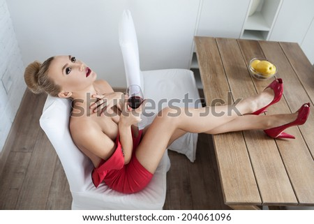 beautiful luxury woman in white interior with glass of red wine - stock photo