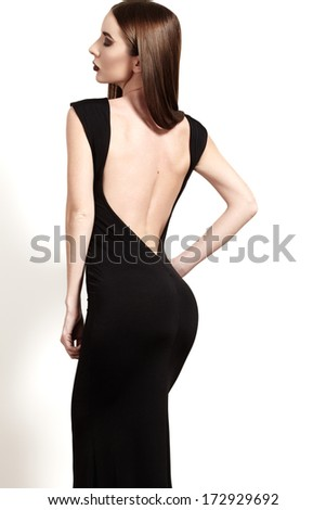 Beautiful luxury woman model posing in black dress with open back on white background. Fashion evening make-up, dark lips, long straight hair, slim voluptuous body shapes.  - stock photo